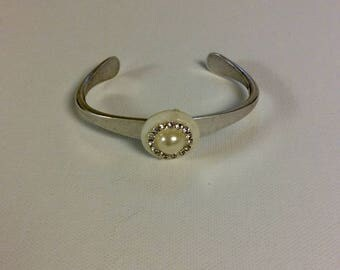 Small pearl surrounded by small rhinestones set on Mother of Pearl on a vintage silver plated Cuff bracelet