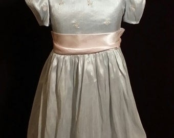 An adorable little girl, blue vintage dress of quality, With pink tie strings, girls size 6X.