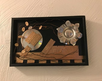 Mixed media upcycled wall art made from used aluminum cans and electronics.