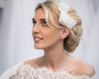 A hair piece, on a comb, with a bow made of delicate French lace.