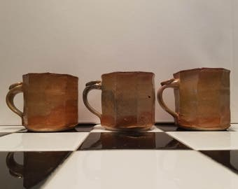 set of three handmade gold and orange mugs, with red and turquoise interior