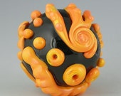a unique round focal done in variegated orange coral on a black base handmade lampwork glass bead - High Contrast Orb