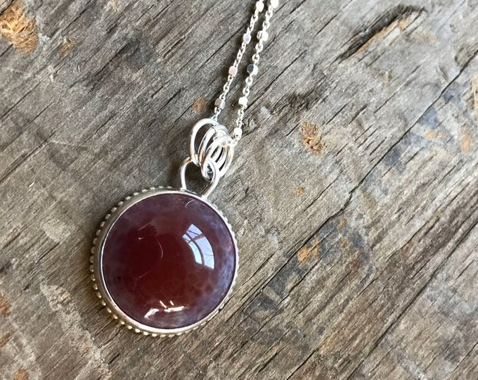 Glowing gemstone necklace sterling silver and reddish pink gemstone that glows with light through it