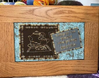 Embroidered plaque in a hardwood frame. Tea pot ,cup and saying