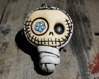 Adorable baby mummy keychain in dirty white. Creepy and cute skull with a blue flower in his eye.