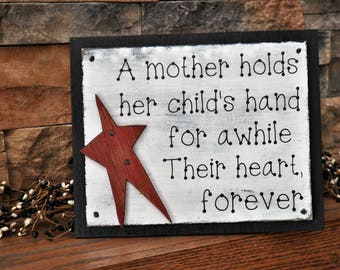 A Mother Holds Her Child's Hand For A While.  Their Heart Forever Wood Sign