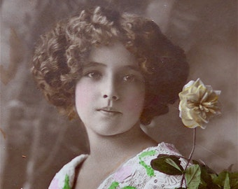 """Greetings postcard, photographic, vintage.  Featuring a young girl holding flowers, Wildt & Kray, London. """"Platino Bromide"""". c early 1920's."""