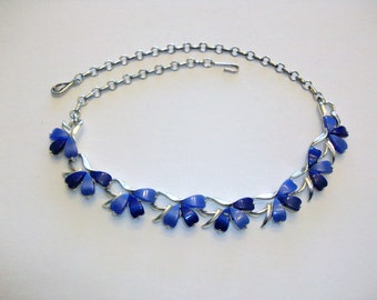 Coro necklace features blue thermoset stones set in silver tone metal.