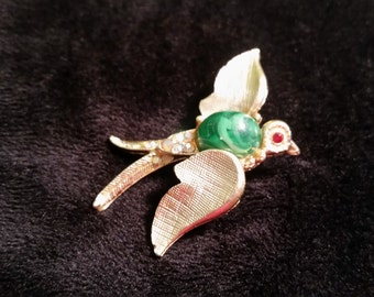 Vintage bird brooch with green glass cabochon body and red rhinestone eyes