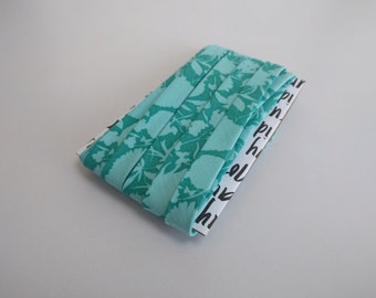 """1/2"""" Double fold bias binding: Aqua, green / blue leaves and silhouettes"""