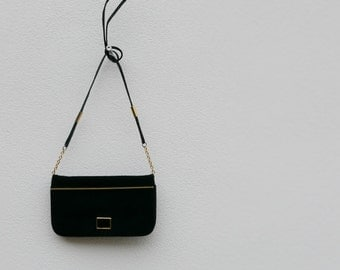 Vintage black leather shoulder bag, lined inside with compartments