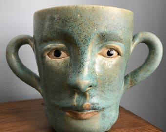 Wheelthrown and handsculpted one of a kind ceramic pottery vessel, cup or mug with face and handles for ears