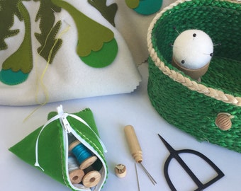 GREEN SEWING BASKET with white black and green sewing accessories and notions.