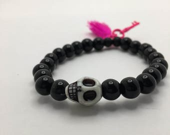 Jet Black Beaded flexible bracelet with a White Skull, Hot Pink Tassel, and Hot Pink Skeleton Key.