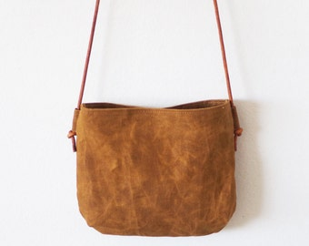 Small brown waxed canvas crossbody bag with round leather straps