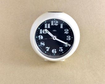 Small white space age Prim wind-up alarm clock with black face and white numerals and hands. Made in Czechoslovakia.