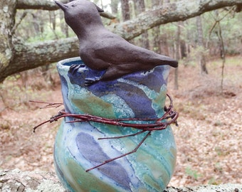 A curious bird perches on the lip of this unique little vase