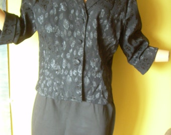 Vintage black dressy overjacket has embossed floral design. Tag marked Lg. Petite. No sign of wear.