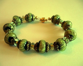 Black, gold and a hint of green.  Small black stripes on these glass beads.