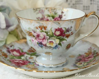 Japan: Stunning footed light blue tea cup and saucer with beautiful bouquet of colorful flowers