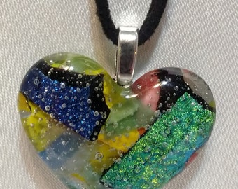 Intriguing Heart shaped fused glass pendant. Multi-colored confetti and dichroic glass appearance.
