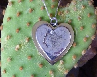 Heart-shaped brass pendant with sterling silver design