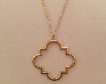 Long gold quatrefoil pendant on gold chain with quatrefoil earrings