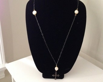Cross and pearl necklace on black chain