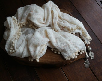 White scarf with pom poms and 'the hand' medallions