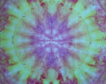 Ice-dyed cotton fabric in shades of red, purple and green on a turqoise background for sewing or quilting