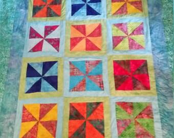 Twin sized bright batik quilt in windmill pattern