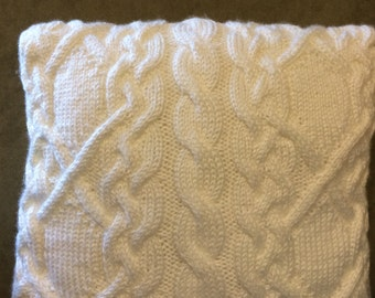 A decorative pillow with hand-knitted cable stitch case