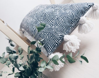 Zebra pillow on the ground with PomPoms