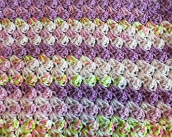 Crochet baby blanket in purples, pinks and green