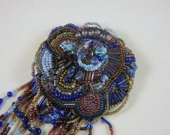 Large beaded brooch in blues and purples with dangles