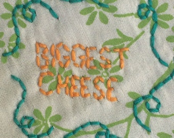 "Hand-embroidered button or patch ""Biggest Cheese"""