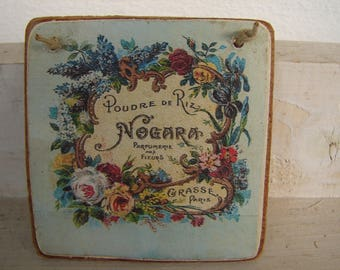 tiny, pale blue, floral French face powder, advertising image, sealed onto wood with string hanger