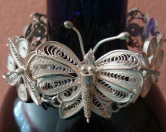 Silver tone filigree bracelet with butterfly and flowers
