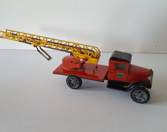 Vintage tin toy firetruck, ladder truck, chippy paint with rubber tires, marked but not clearly
