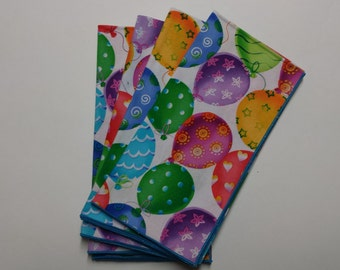 Set of 4 Party dinner napkins with multi colored balloons on white.