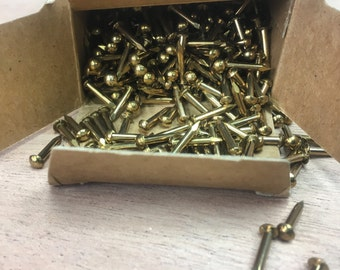 New old stock. Brass eacutheon pins/nails.