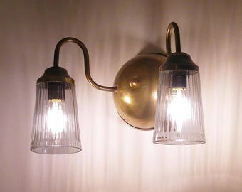 Solid brass wall mounted light fixture with 2 arms and 2 glass shades . Wall sconce with twin U shaped brass arms and two glass shades.