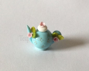 Miniature blue teapot with pink flowers