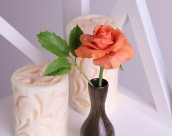Coral rose in a wooden vase