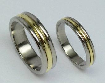Pair of polished titanium, 14 carat gold wedding rings, engagement rings. Titanium, gold jewelry.
