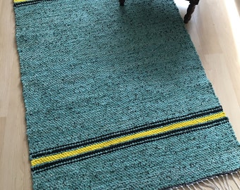 GREEN FLAIR -- Hand-woven green rug with yellow stripes