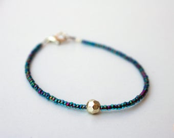 Thin blue lustre seed bead bracelet with feature silver bead.