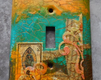 Golden Madonna, light switch cover, mixed media, collage, turquoise and yellow,