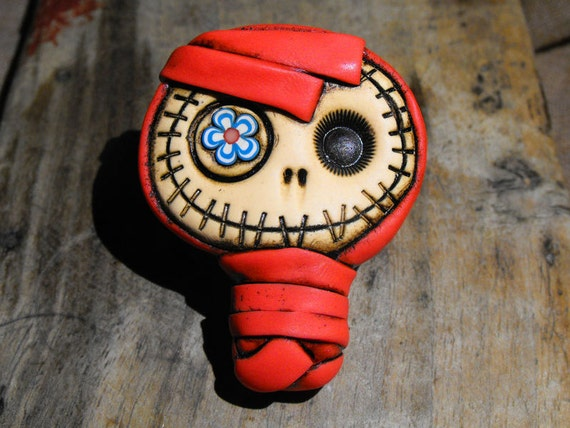Sweet baby mummy brooch bandaged in red with a blue flower in his eye