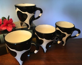 Set of four vintage ceramic cow mugs with pink utters on the bottom from R.H. Macy's